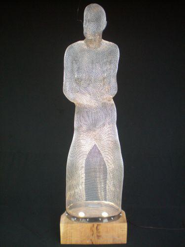 SHE I  Metal net, wooden base, light installation  50 x 30 x 160 cm (sculpture)  40 x 60 x 20 cm (base)